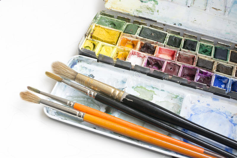 Watercolor box. Artist tools - a well used and messy  and brushes stock image