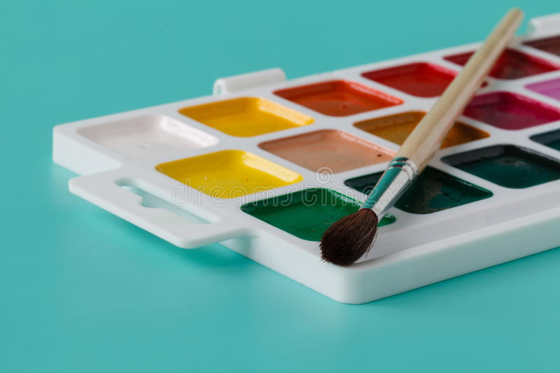 Watercolor paints in a box with a brush royalty free stock photography
