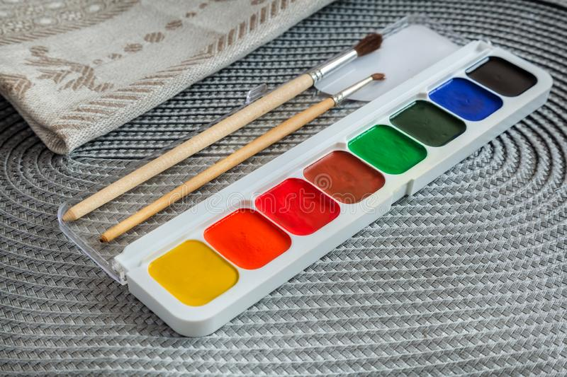 Watercolor paints in a case and brushes royalty free stock photography