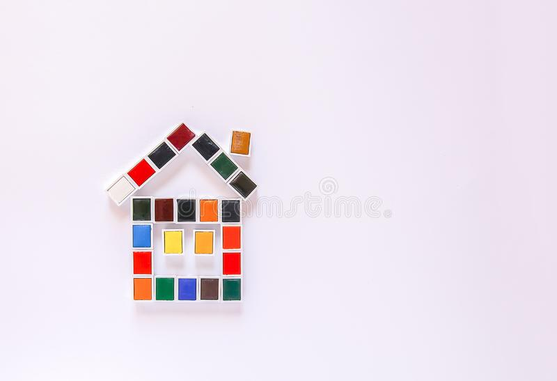 Watercolor paints in the shape of  house on white background. Flat lay, top view. Watercolor paints in the shape of funny house on white background. Flat lay royalty free stock photography