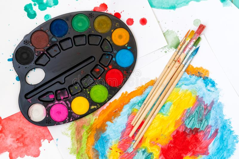 Watercolor palette, brushes and paper royalty free stock image