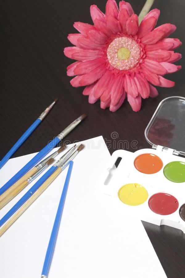 Watercolors and brushes on a dark surface. Nearby is an artificial flower in a vase for still life. Subjects for creativity. stock photography