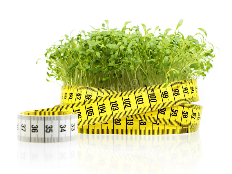 Watercress diet. Watercress with measuring tape (diet) on white with reflection royalty free stock photography