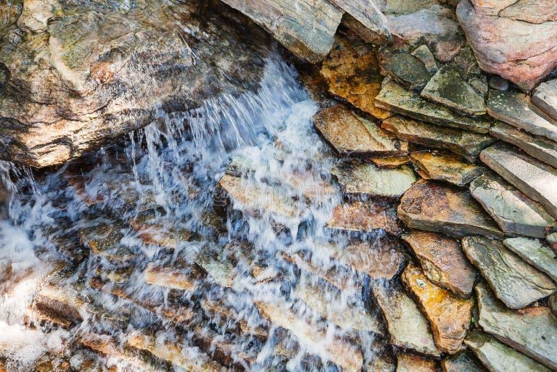 Waterdaling op donkere decoratieve steen stock fotografie