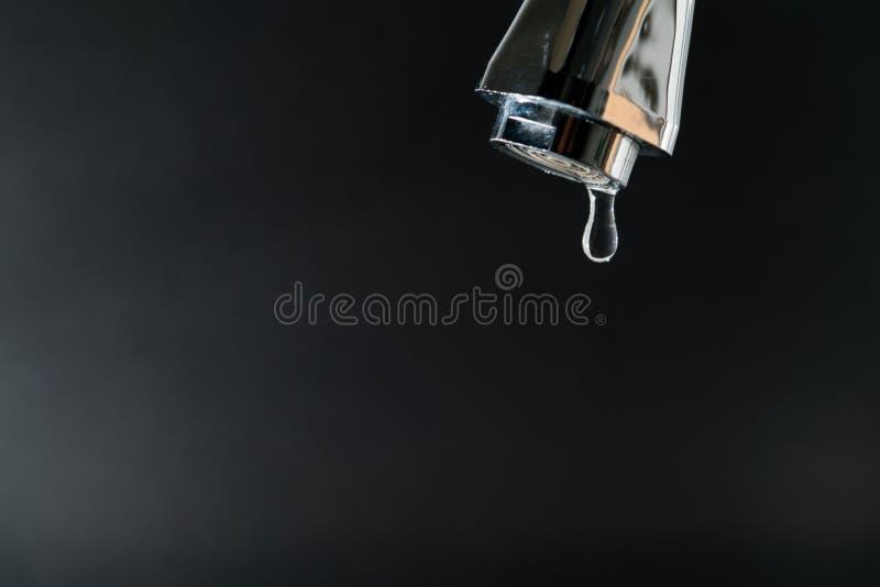 Waterdaling op tapkraan met zwarte achtergronden, de dagconcept van het wereldwater met exemplaarruimte stock foto