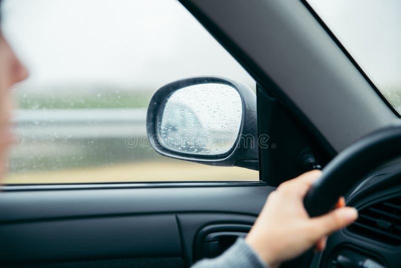 Waterdalingen op autospiegel stock fotografie