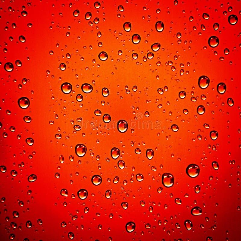 Waterdalingen op rode achtergrond stock foto