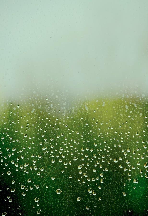 Waterdalingen van een april-douche op een vuile ruit van glas royalty-vrije stock foto's