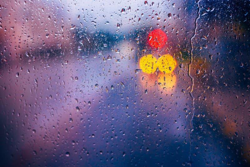 Waterdalingen van regen op blauwe glasachtergrond De Lichten van straatbokeh royalty-vrije stock foto's