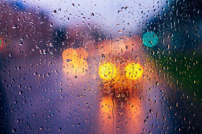 Waterdalingen van regen op blauwe glasachtergrond De Lichten van straatbokeh royalty-vrije stock afbeeldingen