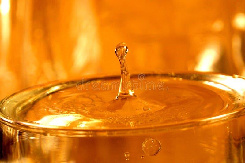 Waterdrop in goud stock foto's