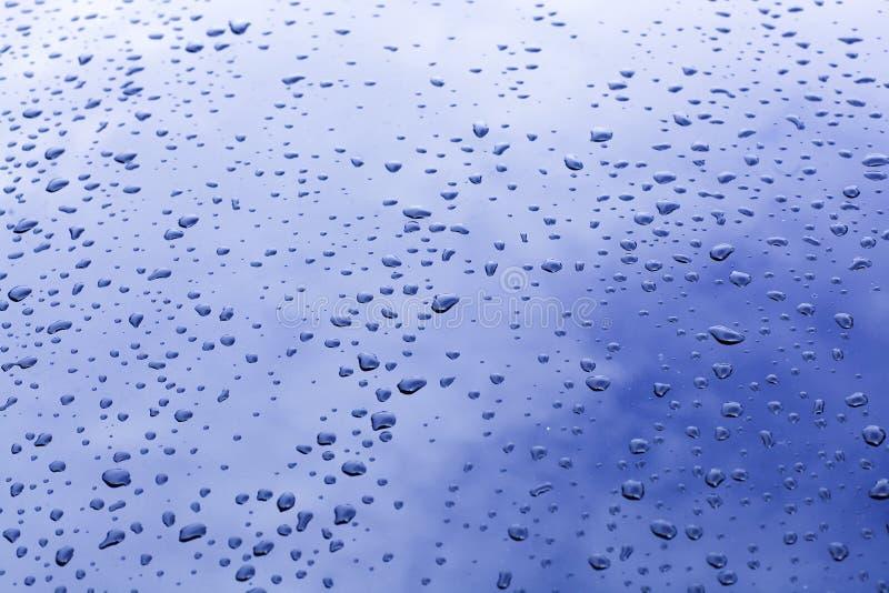 Waterdrop på exponeringsglas med reflexion av blå himmel royaltyfri bild