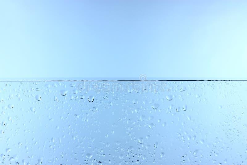 Waterdrops em Glas na frente de um fundo azul imagens de stock