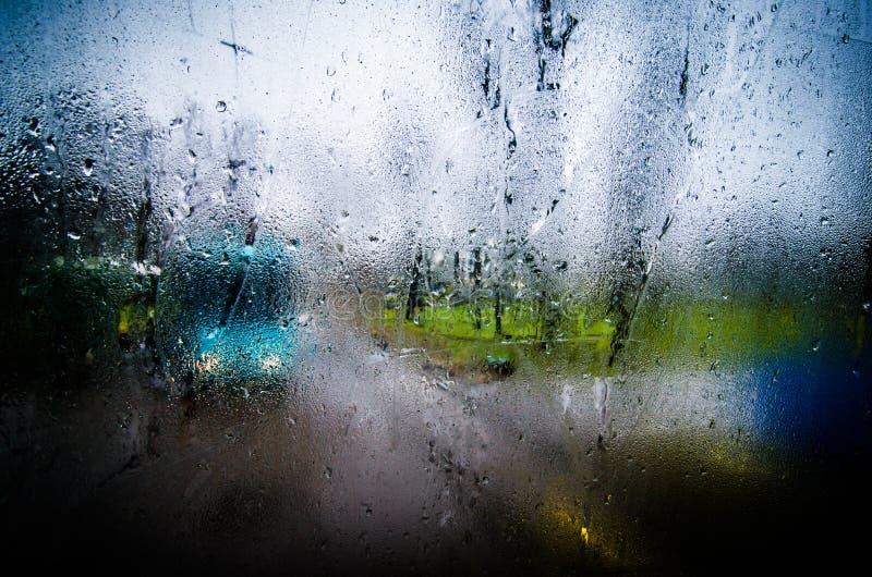 Waterdrops en ventanas de una superficie del vidrio con el fondo del paisaje urbano del primer foto de archivo