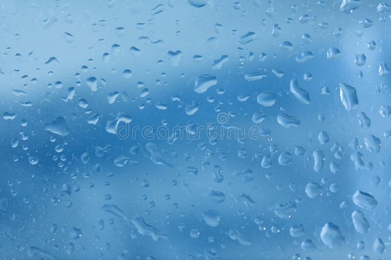Waterdrops on a glass blue coloured background royalty free stock image