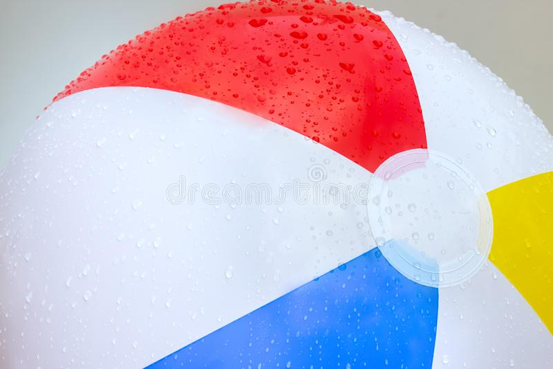 Waterdruppels op een strandbal met rode, gele, blauwe en witte strandballen die communiceren met de zomer royalty-vrije stock foto