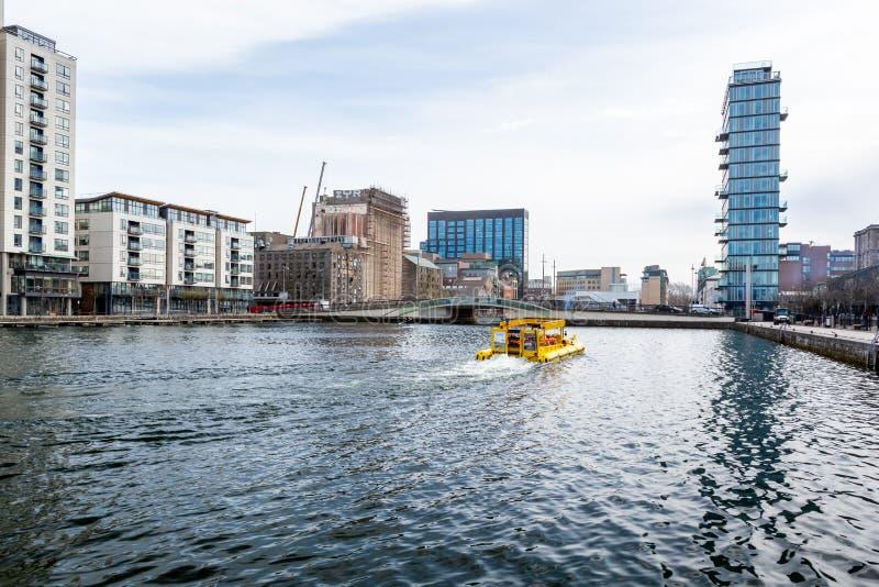 Waterenrand met een gele boot van de toeristencruise/voertuig in het centrum van Dublin stock afbeelding