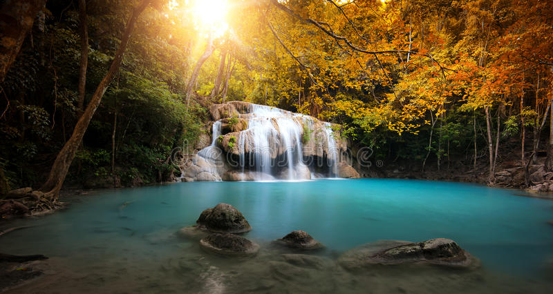 Waterfall in autumn forest with bright sun light stock photo