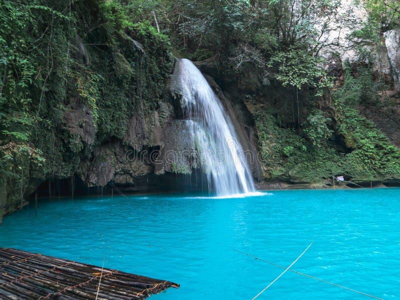Bamboo raft on turquoise waterfall pool in Kawasan Falls in Cebu Island. Waterfall with bamboo raft on the turquoise water pool at Kawasan Falls in Cebu Island stock images