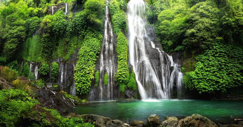 Waterfall cascade in tropical rainforest with rock and turquoise blue pond.  royalty free stock image