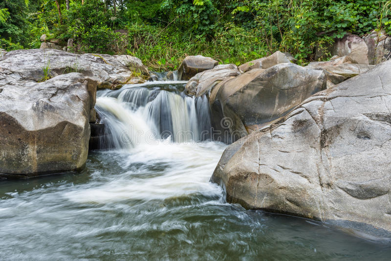 Waterfall cascades flowing over flat rocks in forest royalty free stock photos