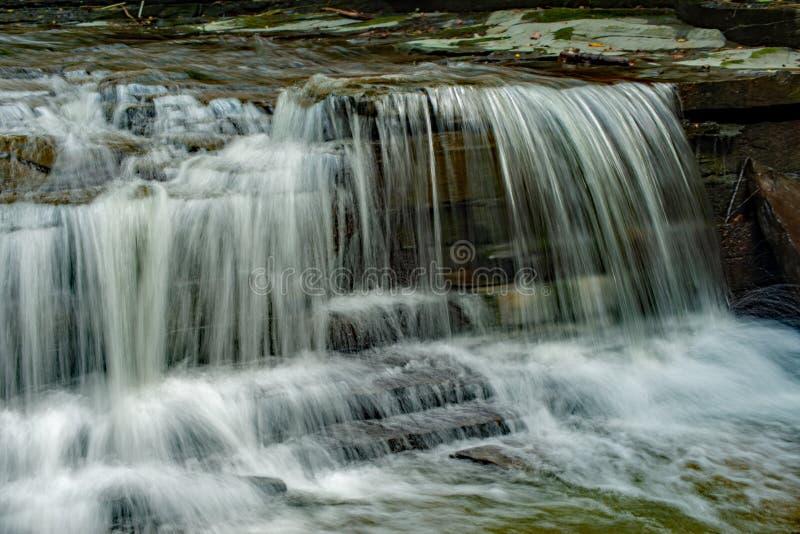 Waterfall cascading on the creek stock photo