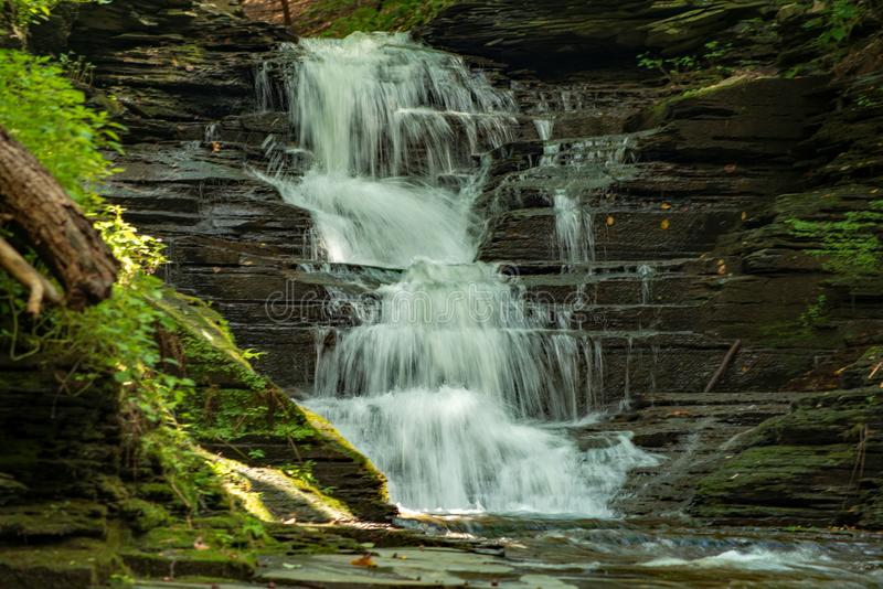 Waterfall cascading on the creek stock images