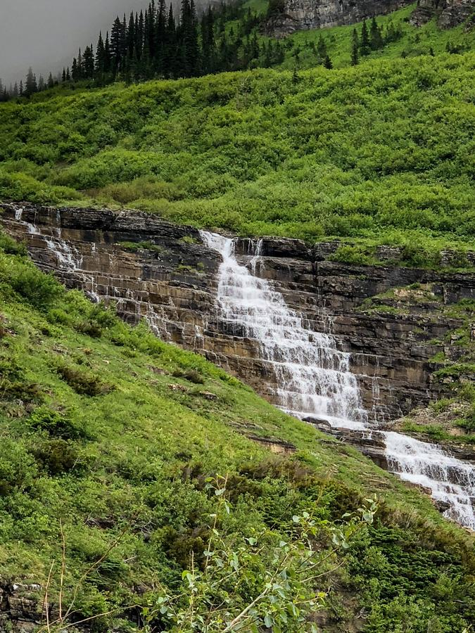 Waterfall cascading down rocks at national park. Scenic view of a waterfall cascading down rocks from the top of a mountain at Glacier National Park in Montana stock photos
