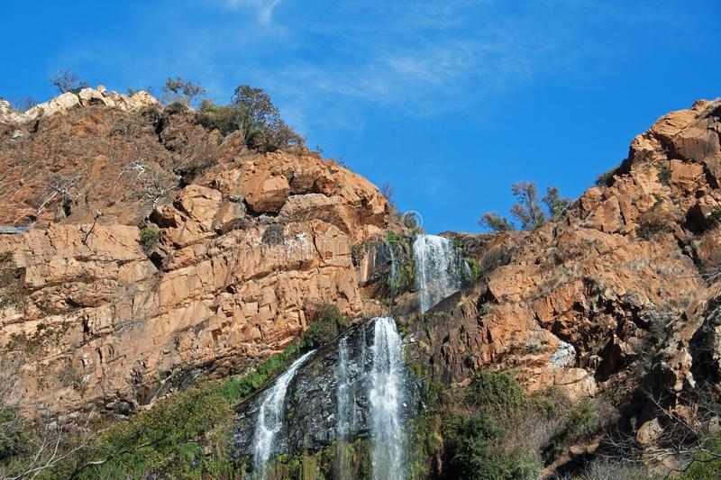 WATERFALL CASCADING OVER ROCK AND VEGETATION. Expanse of blue sky with waterfall falling over a rocky cliff and smudge of cloud royalty free stock image