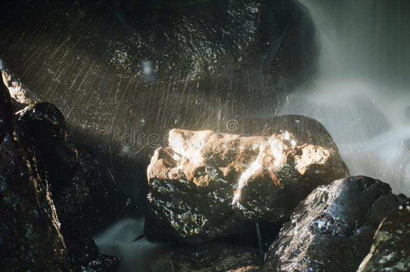 Waterfall in cave behind rock in forest stock photo