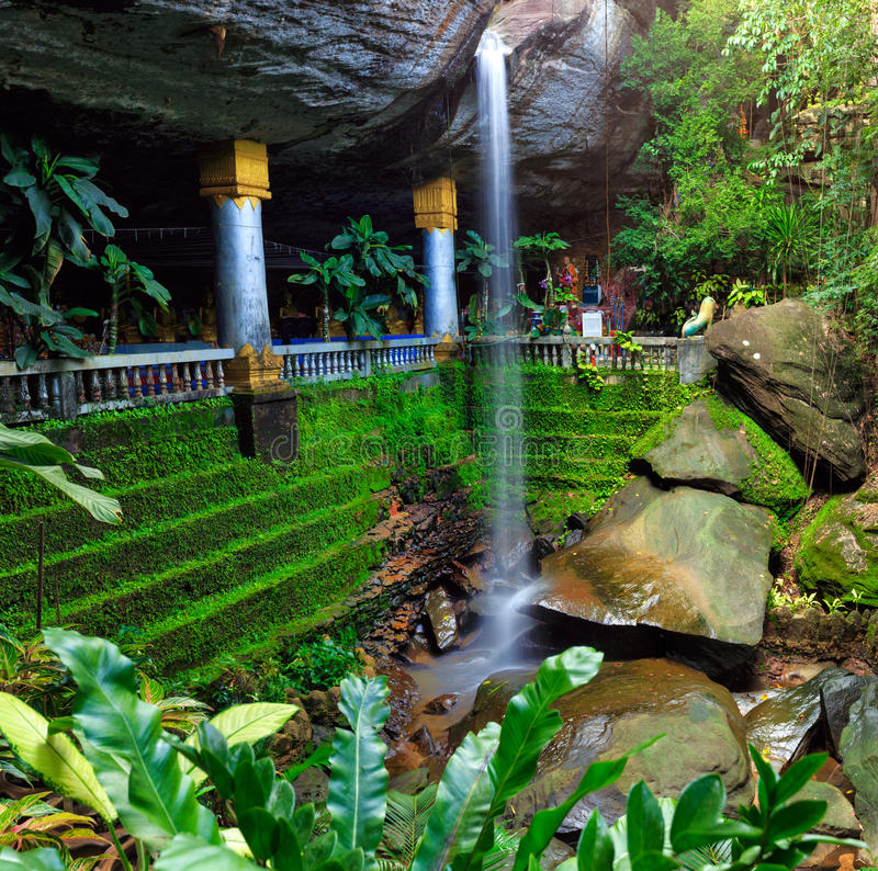 Waterfall and the cave temple at Ubon Ratchathani in Thailand. Waterfall in the forest and the cave temple at Ubon Ratchathani in Thailand royalty free stock photos
