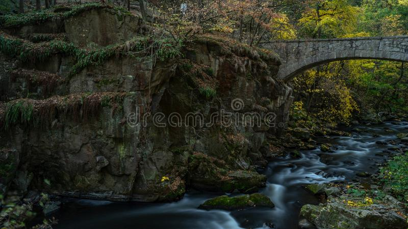 Waterfall with colorful leaves and green moss in autumn. Germany in the Bode Valley. Long exposure royalty free stock image
