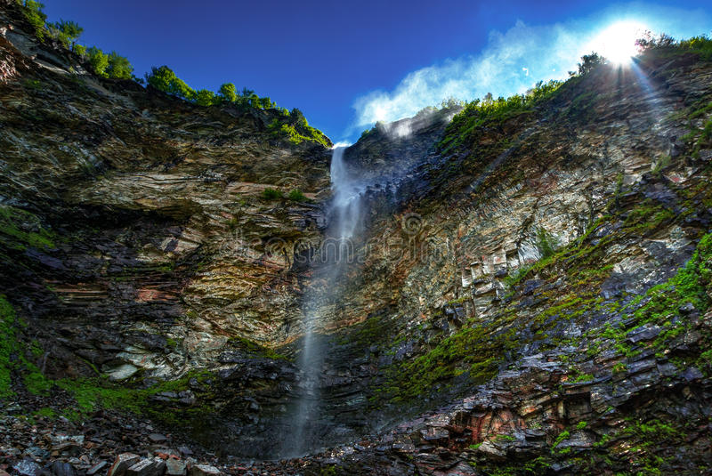 Waterfall down a rocky cliff stock photography