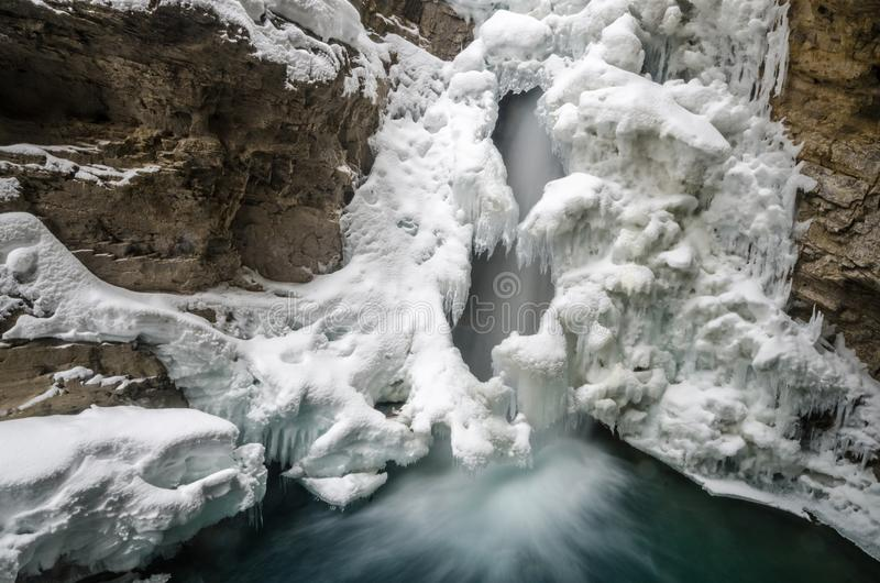 Waterfall flowing beneath cover of snow into blue depths stock images