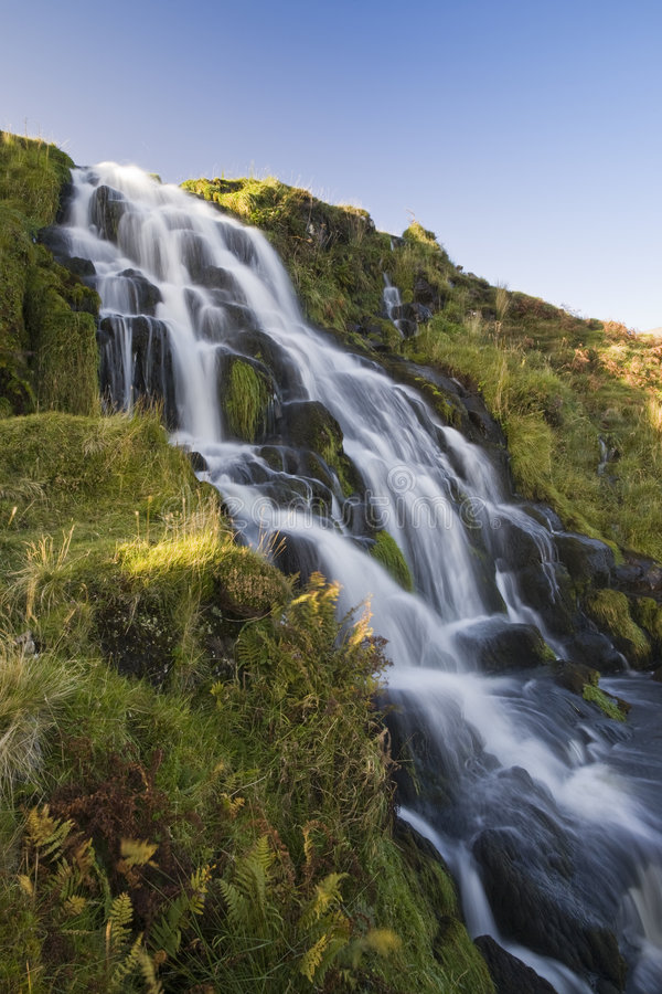 Waterfall flowing down hill with blue sky royalty free stock photos