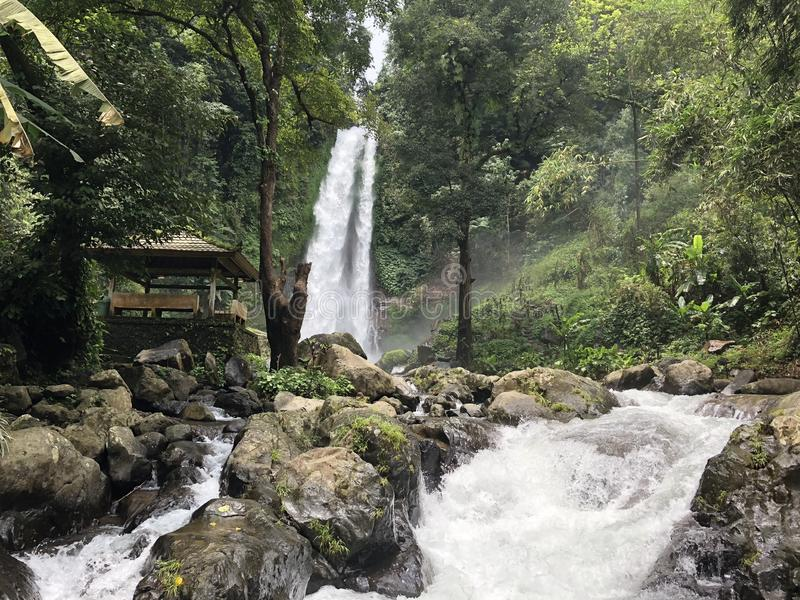 Waterfall flowing down in the middle of rocks near a wooden arbor with forest in the background stock images