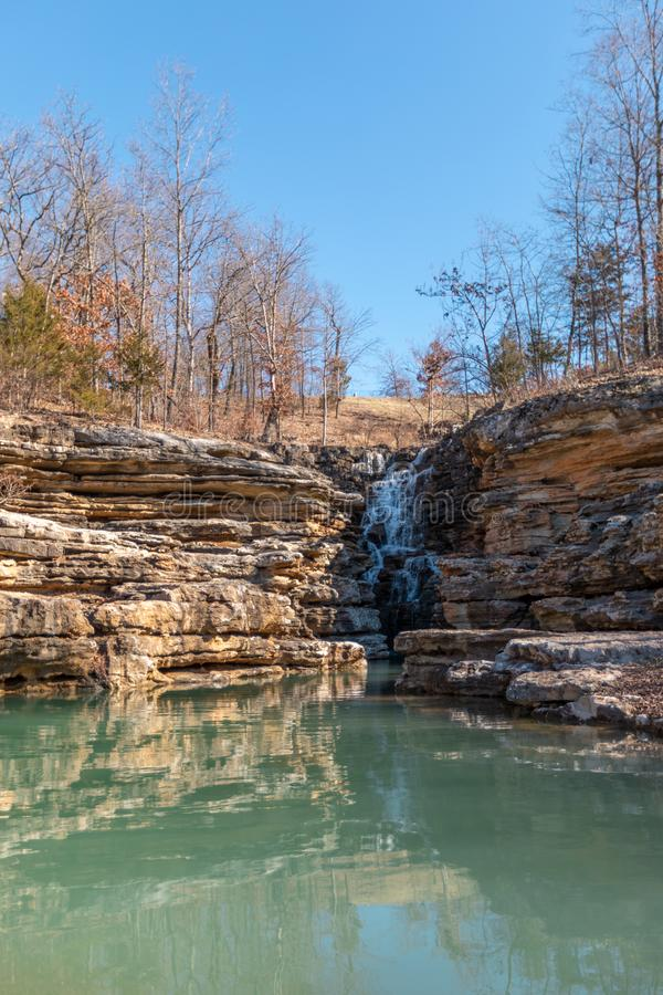 Waterfall over green blue pond royalty free stock photo