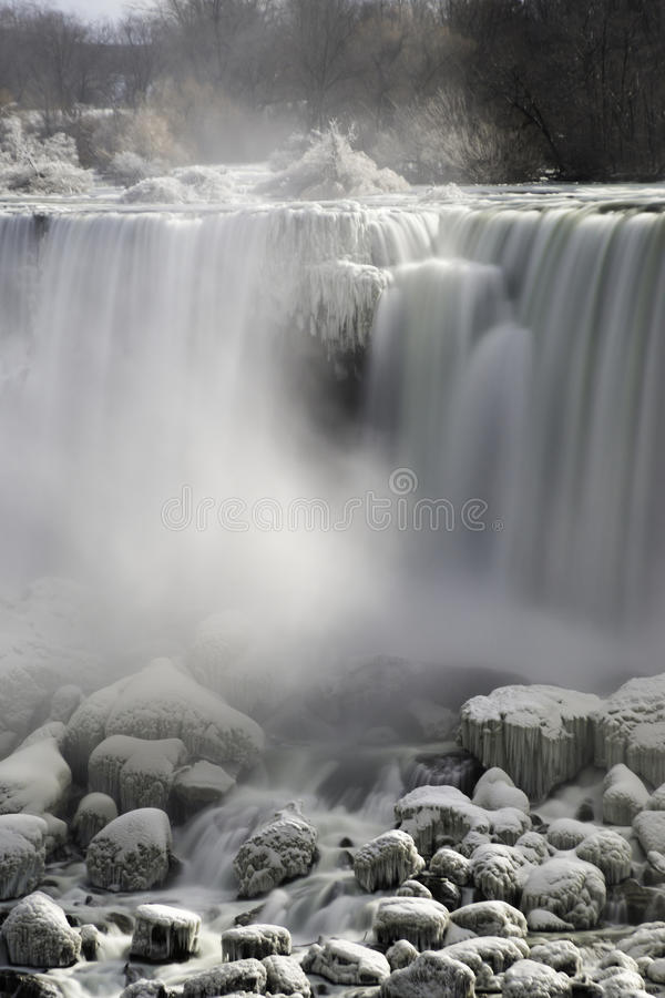 Waterfall flowing over snow covered rocks, mist rising, frost co stock photos