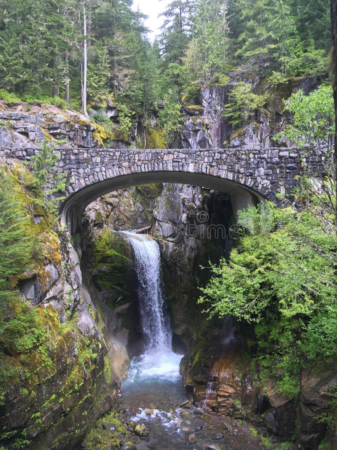 Waterfall under a stone bridge stock images