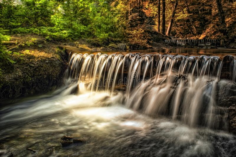 Waterfall in a forest. Abstract lanscape of moving nature from summer to autumn.  royalty free stock images