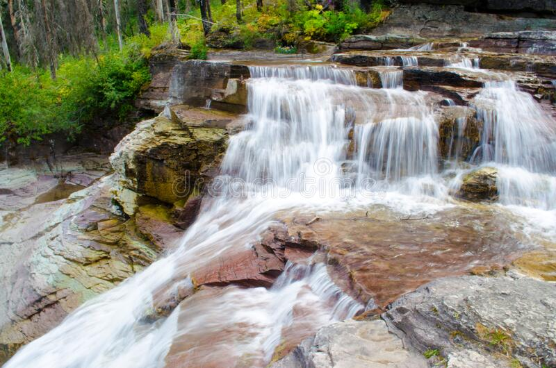 Waterfall In Forest. A waterfall flowing over rocks and boulders in a forest royalty free stock photos
