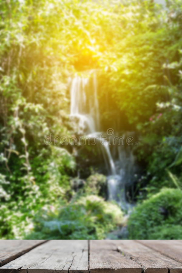 Waterfall in garden with wood table for display your product. Waterfall in garden with wood table for display or montage your product royalty free stock images