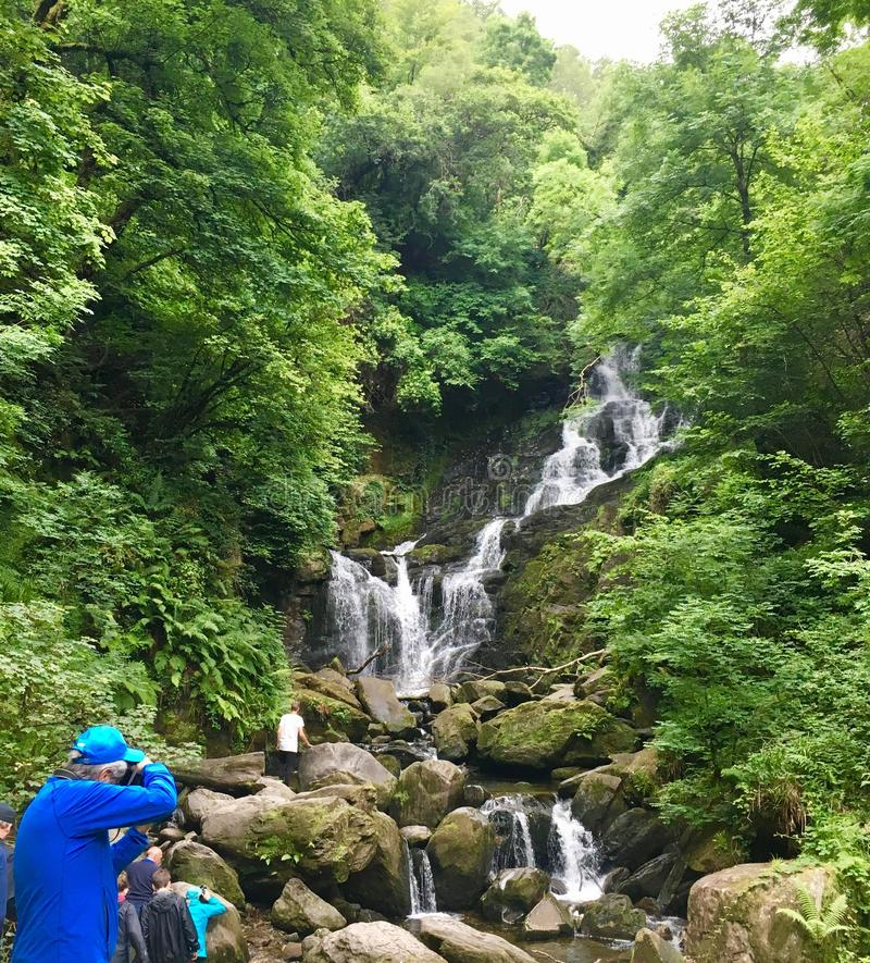Waterfall in Killarney National Park. An avid photographer is trying to capture the beauty of the waterfall in Ireland in Killarney National Park stock image