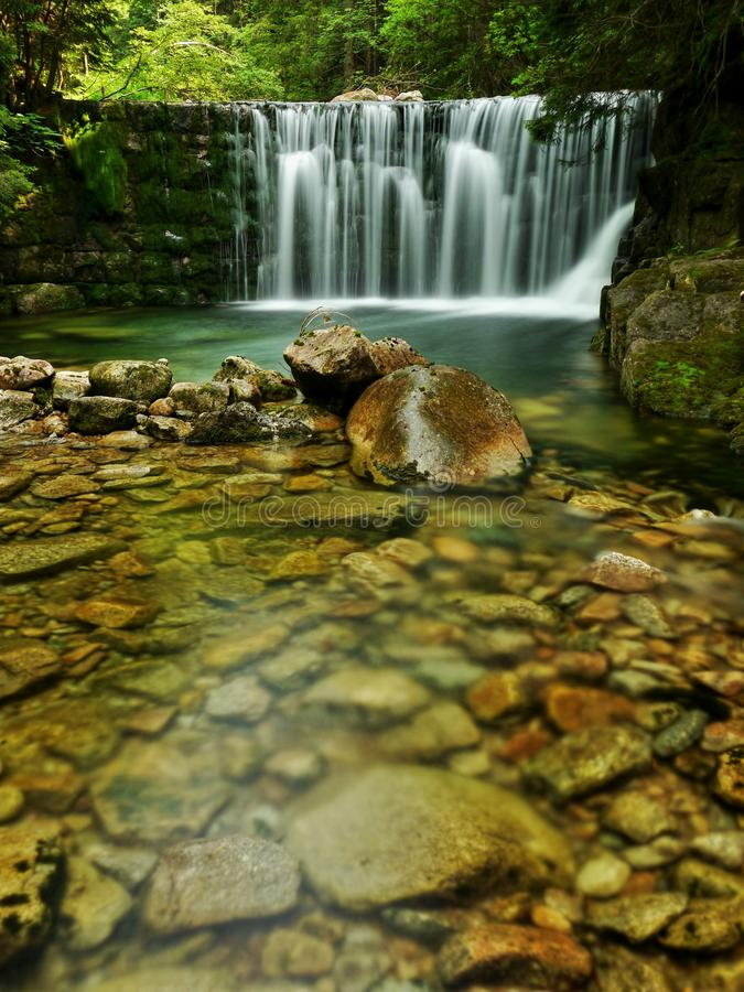 Waterfall with a lagoon on mountain stream royalty free stock photography