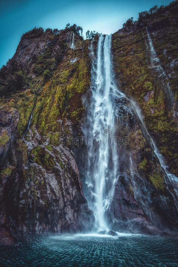 Waterfall in Milford Sound from low angle. Stirling Falls waterfall in Milford Sound in New Zealand, viewed from low angle with waves spreading on water surface stock photo