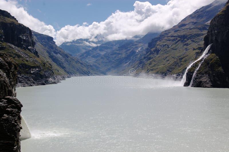 Waterfall on mountain lake stock image
