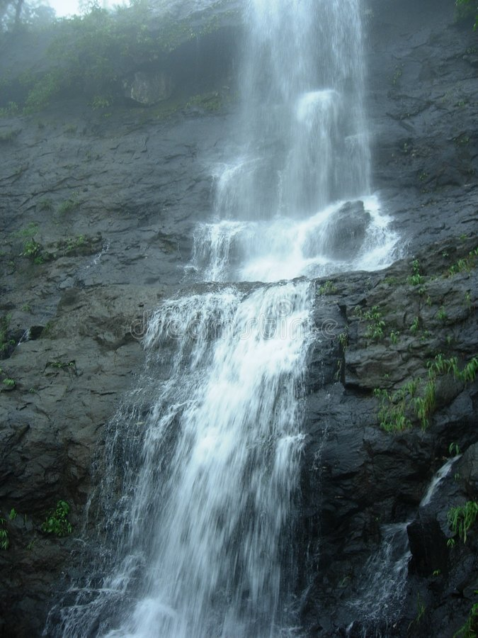 Waterfall over cliff. Scenic view of waterfall over cliff or mountainside royalty free stock images