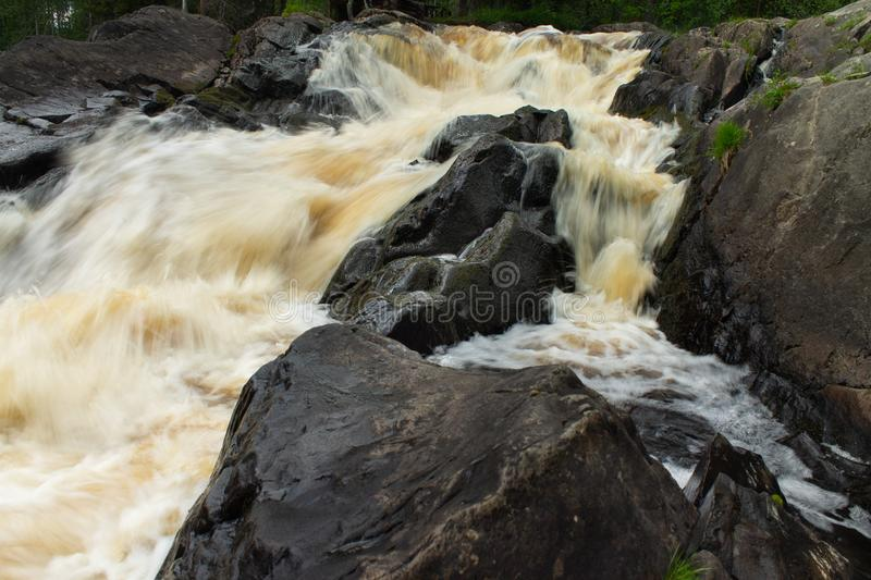 Waterfall over granite rocks fast water flow. Beautiful waterfall landscape on granite stones. fast water flow with blur effect stock photo