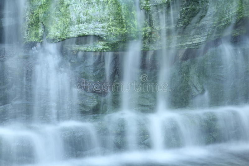 Waterfall over the green rock