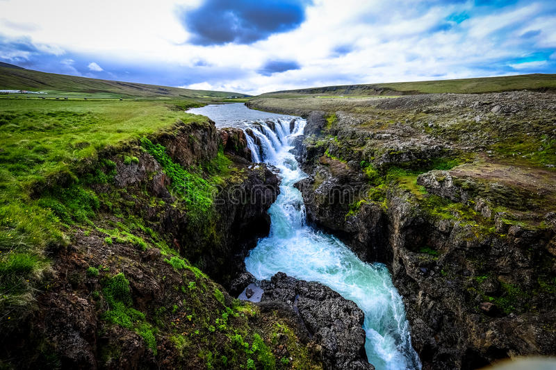 Waterfall over rocky cliffs stock image